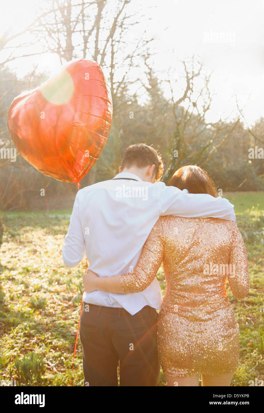 Paar im Park hält herzförmige Ballon, hintere Ansicht Stockbild