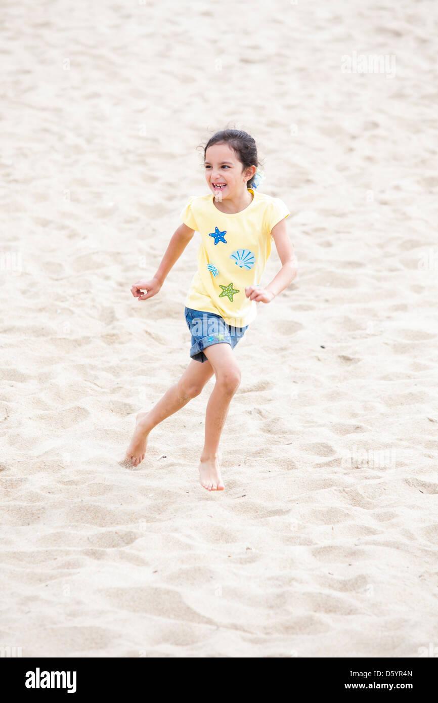 Mädchen am Strand laufen Stockbild