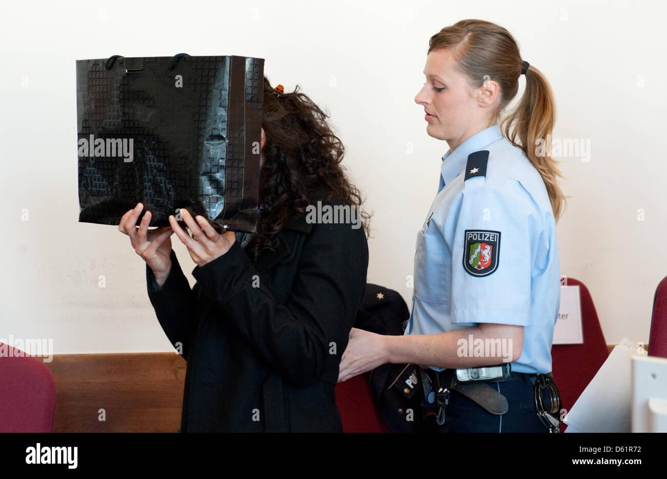 Ein Angeklagter verbirgt sich hinter einer Tasche vor der Verhandlung am Landgericht in Detmold, Deutschland, 30. Stockfoto
