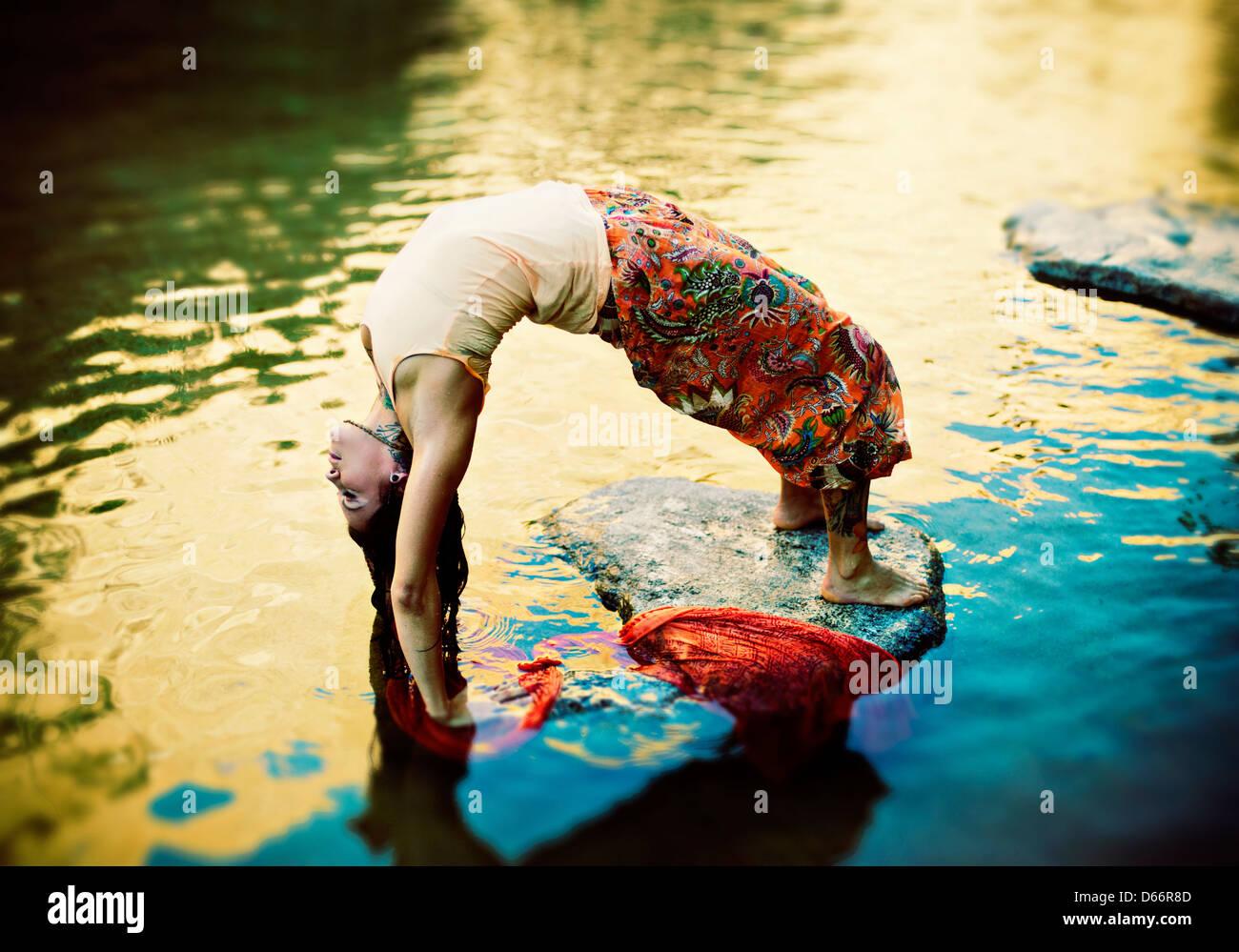 Yoga-Frau im Freien in Yoga pose Urdhva Dhanurasana in einem bunten Teich. Stockbild
