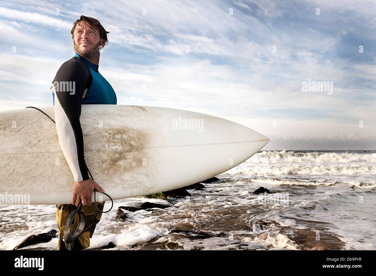 Surfer tragen Board am Strand Stockbild