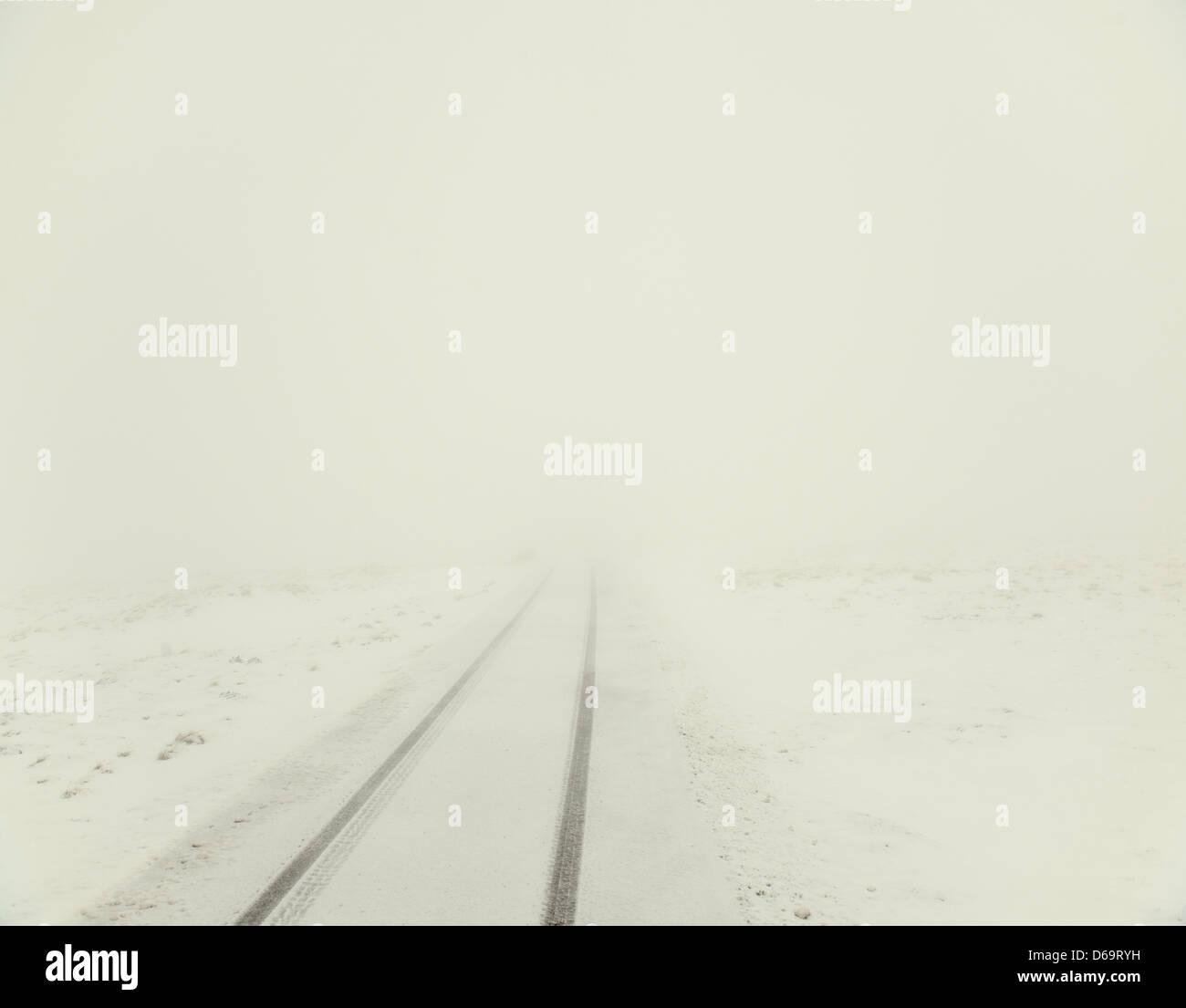 Tracks auf Landstraße durch Schnee verdeckt Stockbild