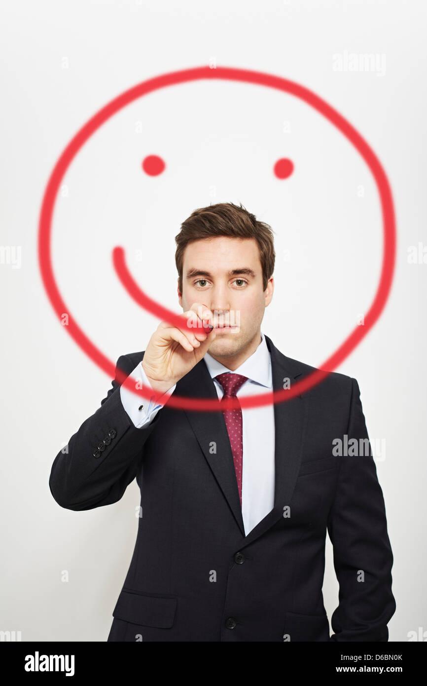 Geschäftsmann zeichnen Smiley-Gesicht in Luft Stockbild