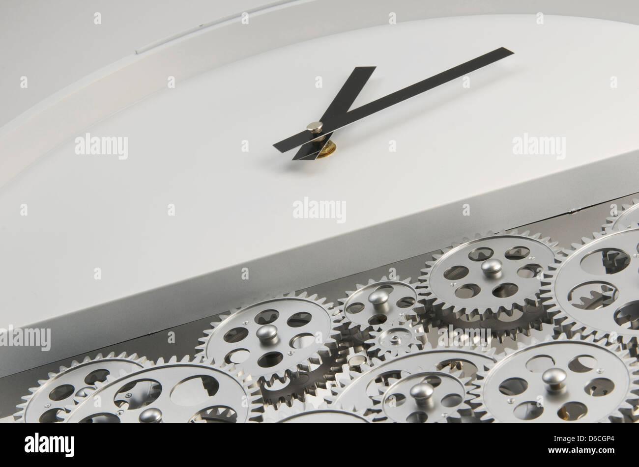 Schräge Schuss eines weißen konfrontiert Uhr mit schwarzen Händen und Zahnräder in der unteren Stockbild