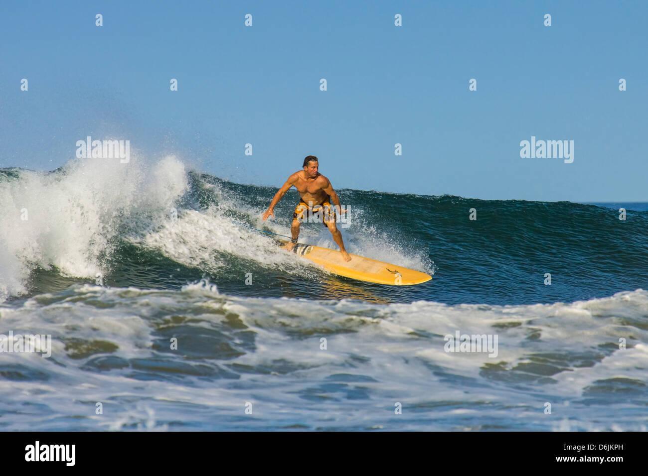 Surfer am Longboard auf Welle am beliebten Playa Guiones Surf Beach, Nosara, Nicoya Halbinsel, Provinz Guanacaste, Stockbild