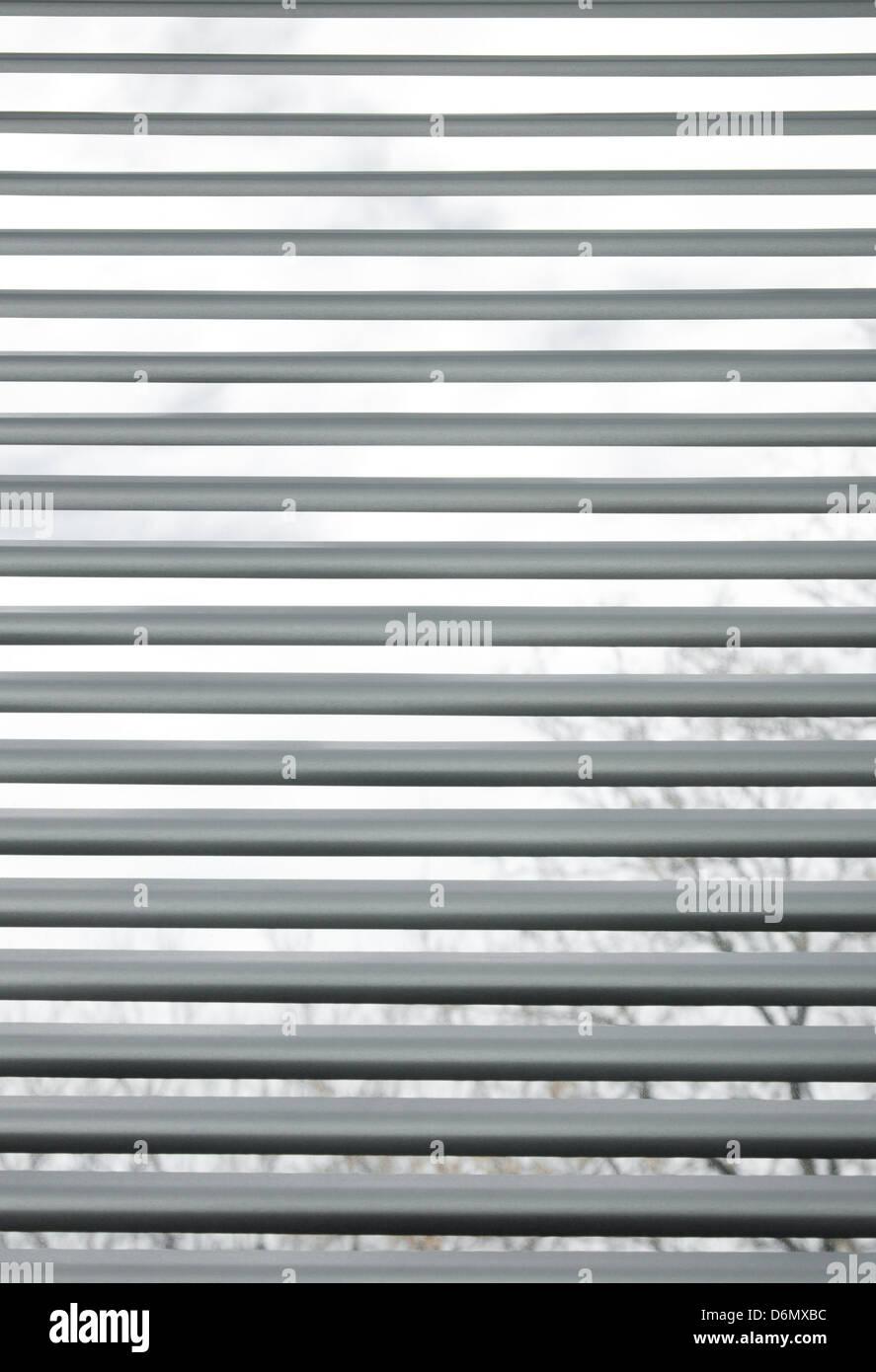 Bäume durch halb geschlossenen metallischen Jalousien in einem Fenster gesehen. Stockfoto