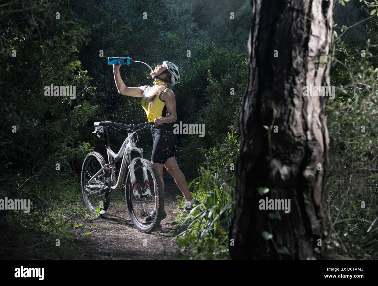 Frau Trinkwasser mit ihrem Mountainbike. Tarifa, Cádiz, Andalusien, Spanien. Stockbild