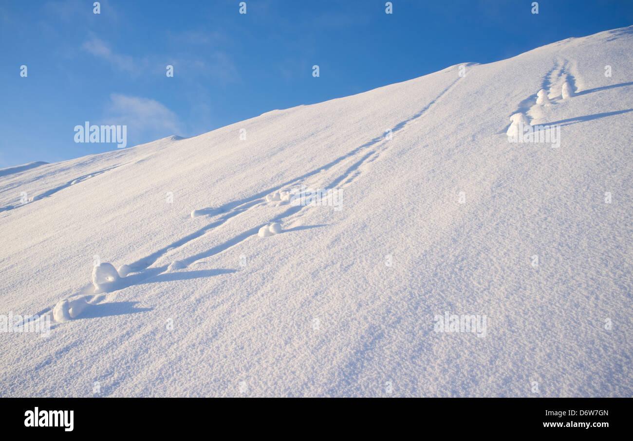 Schneebälle auf steilen Hügel hinunter Rollen Stockbild