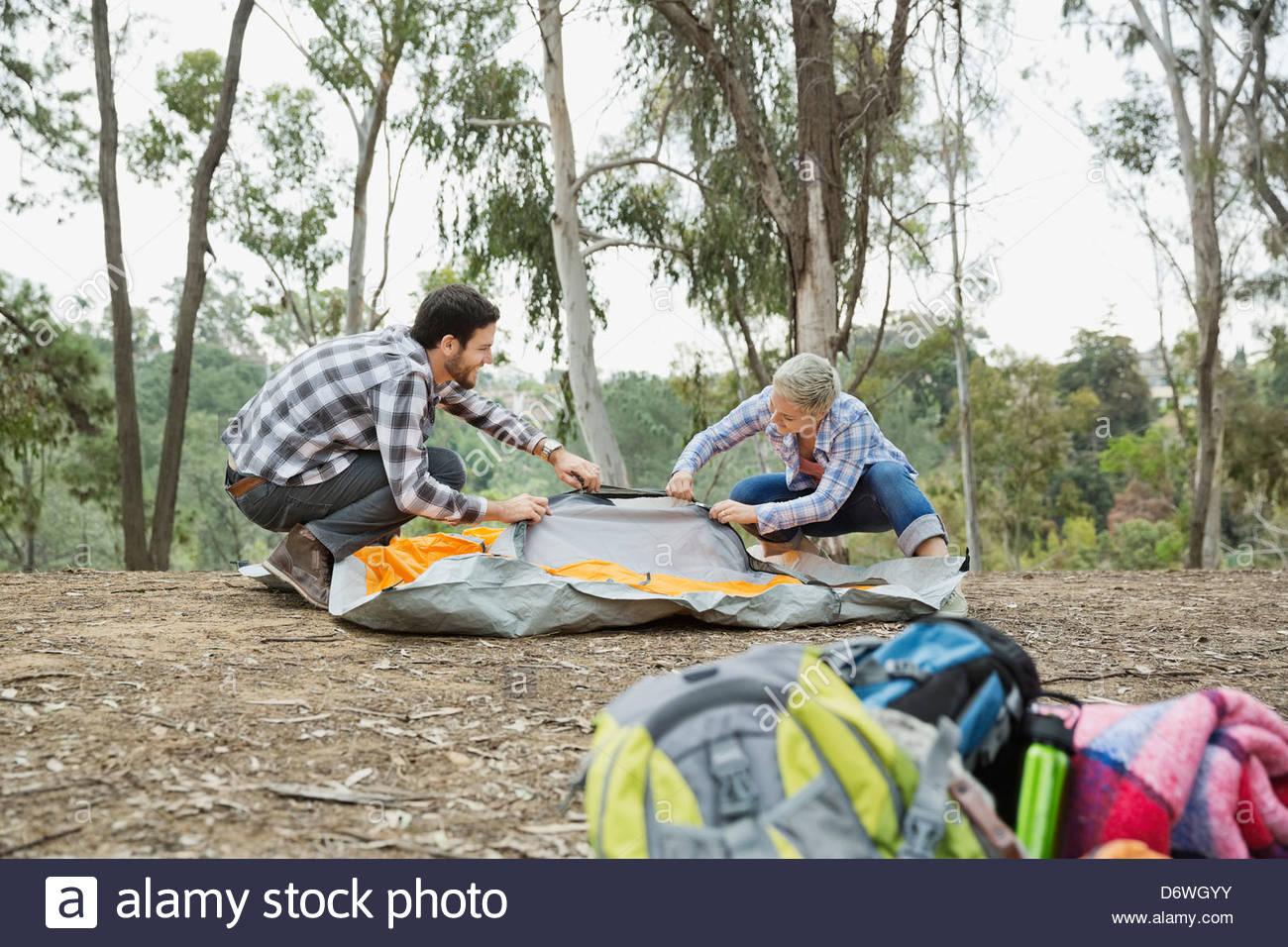 Paar einrichten Zelt im Wald mit Rucksäcken im Vordergrund Stockbild