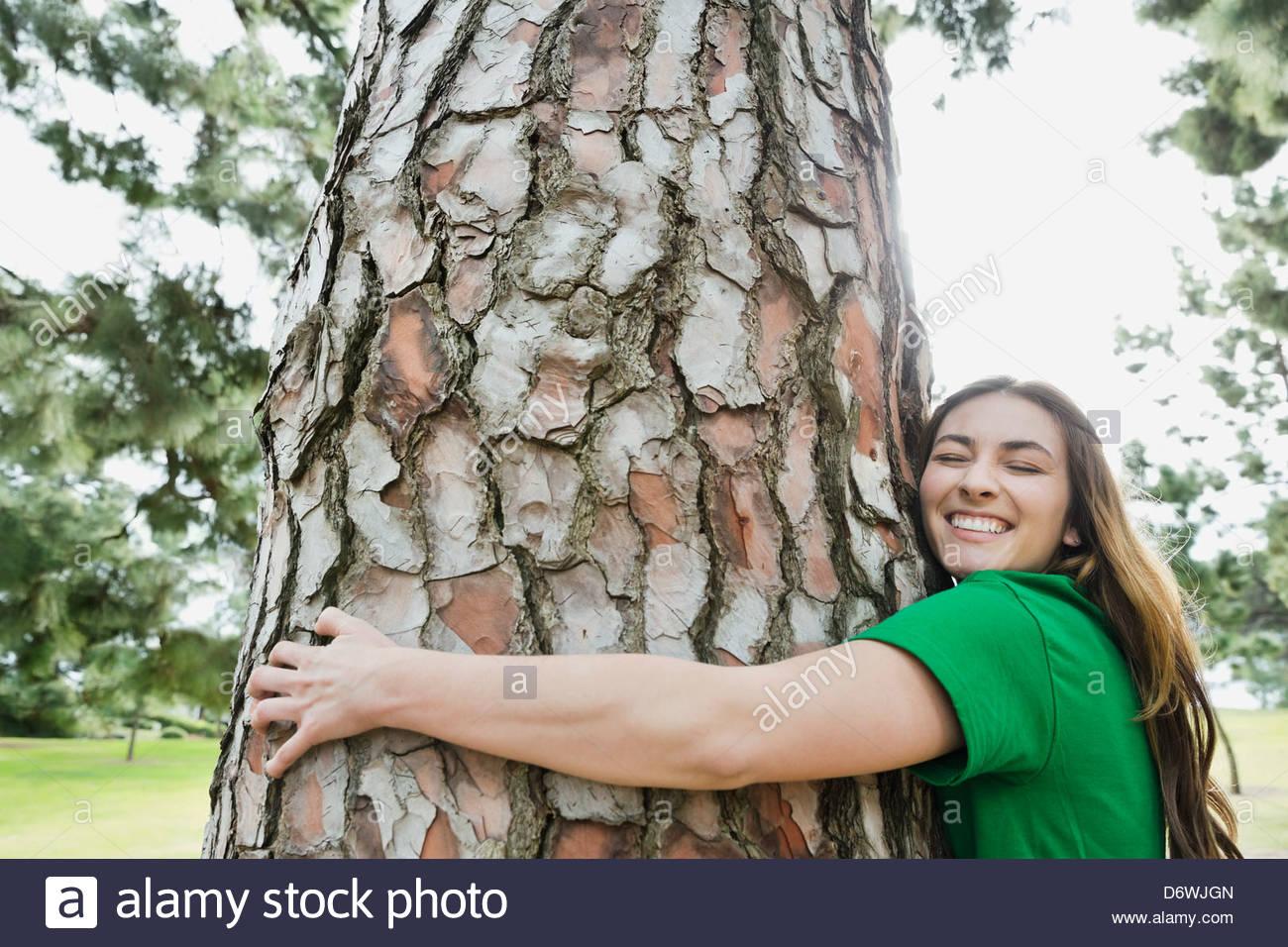 Seitenansicht der glückliche junge Frau umarmt Baum im park Stockbild