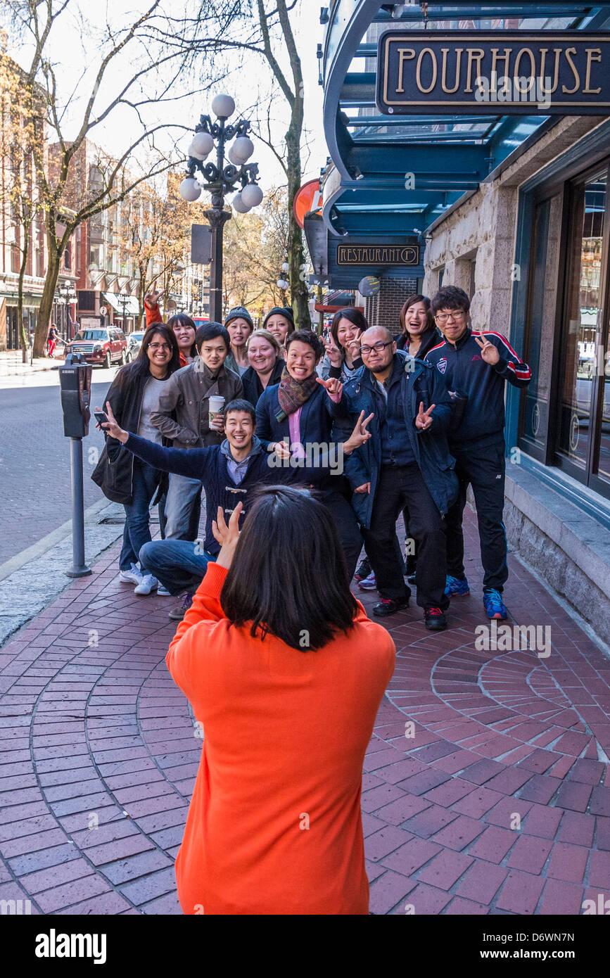 Asiatische Reisegruppe posiert für Bild auf Bürgersteig in Gastown. Stockbild