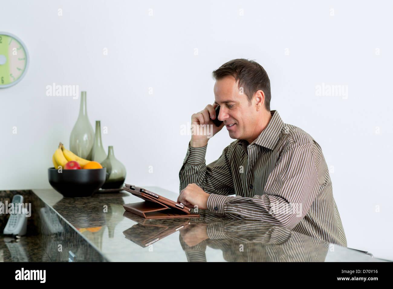 Geschäftsmann am Telefon zu sprechen und mit Blick auf eingebrachten Computer in Küche Stockbild