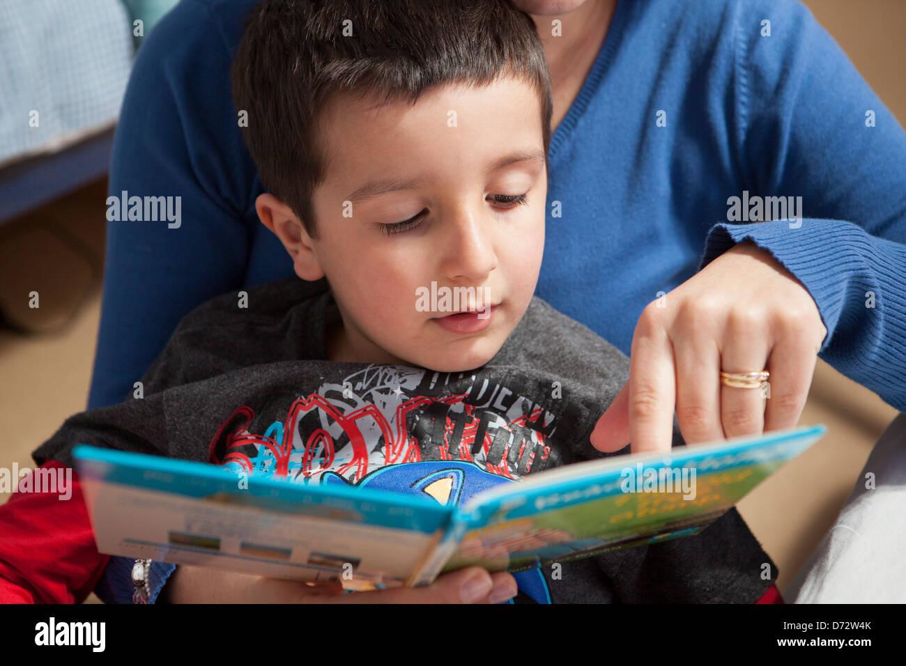 Mutter hilft Kind zu lesen Stockbild