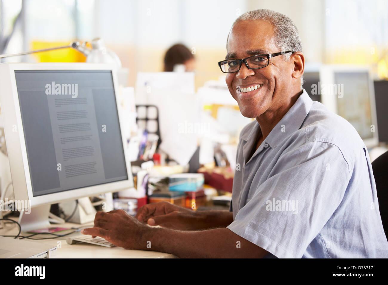 Mann am Schalter In belebten Kreativbüro arbeitet Stockbild
