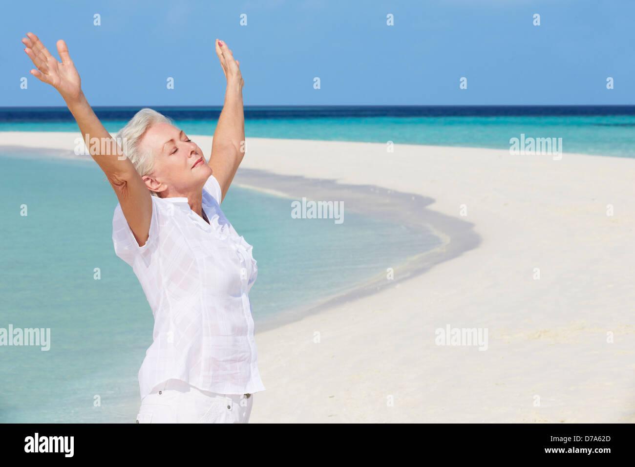 Ältere Frau mit ausgestreckten am schönen Strand Stockbild