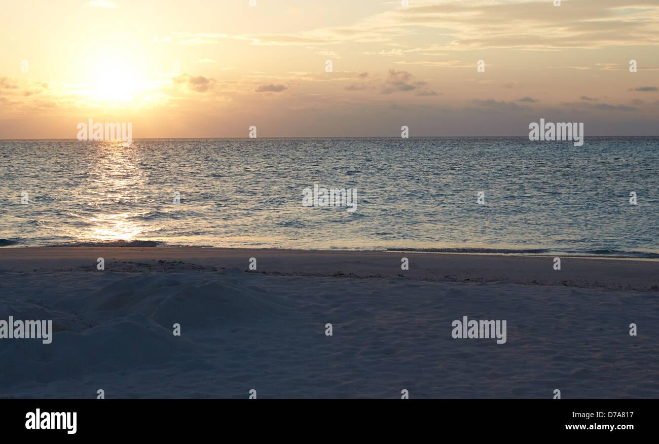 Sonnenuntergang über schönen einsamen Strand Stockbild