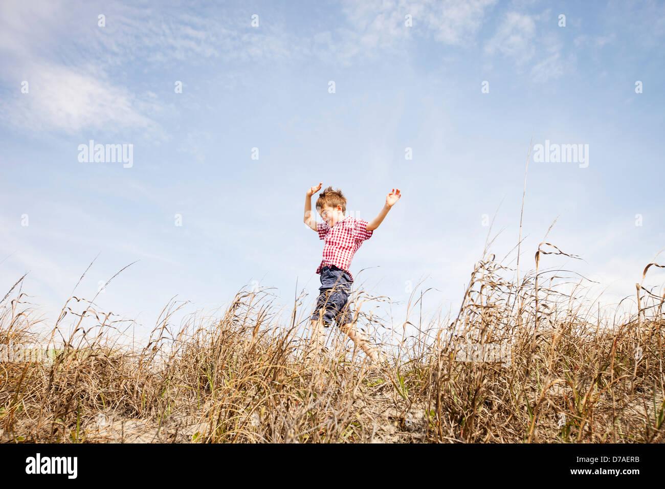 Kind läuft durch Dünen Stockbild