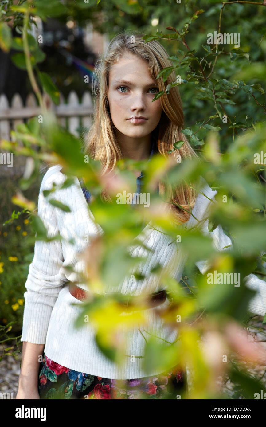 Schöne Teen hinter Baum im Garten Stockbild