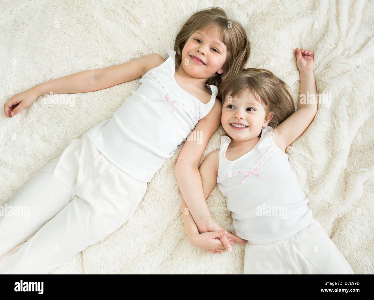 glückliche kleine Schwestern liegen wieder Draufsicht Stockbild