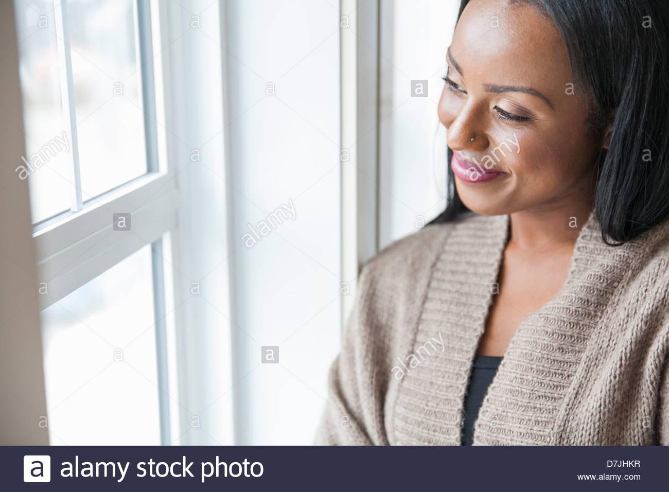 Lächelnde Frau schaut aus Fenster zu Hause Stockbild