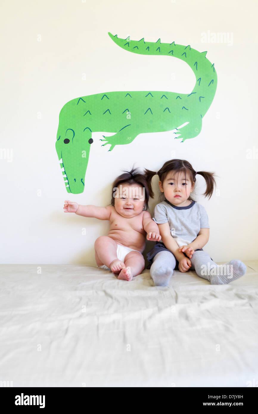 zwei niedliche koreanische amerikanische kinder sitzen auf bett posiert f r die kamera vor. Black Bedroom Furniture Sets. Home Design Ideas