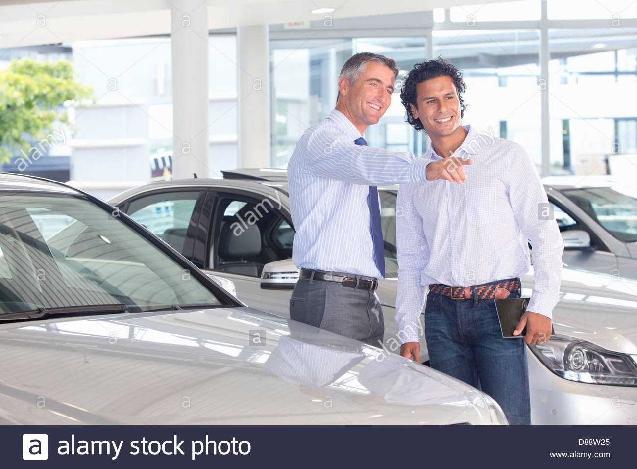 Lächelnde Verkäufer zeigt Kunden Autos im Autohaus Autohaus Stockbild
