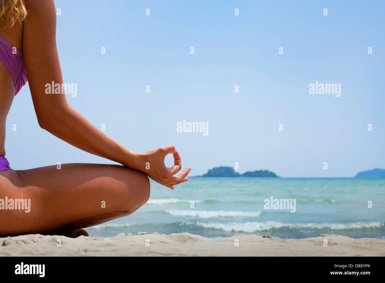 Yoga Hintergrund, Frau im Lotussitz meditieren am Strand Stockbild