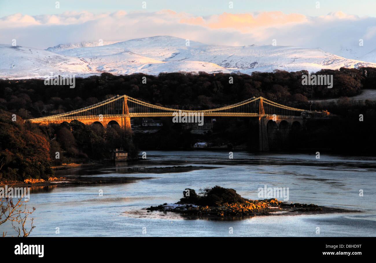 Laden Sie dieses Alamy Stockfoto Die Menai Aufhebung-Brücke, erbaut im Jahre 1826 von Thomas Telford, bei Sonnenuntergang mit Schnee bedeckten Berge von Snowdonia im Hintergrund - D8HD9T