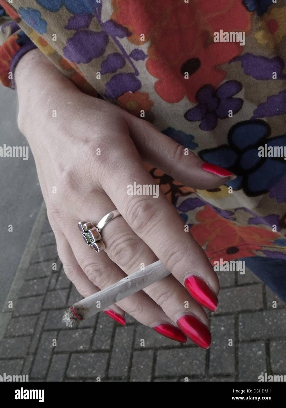 Laden Sie dieses Alamy Stockfoto Lady-Raucher eine hausgemachte Roll hochhält, Rauchen außerhalb eines Gebäudes in England, Großbritannien, wo ein Rauchverbot in öffentlichen Räumen in Kraft - D8HDMH