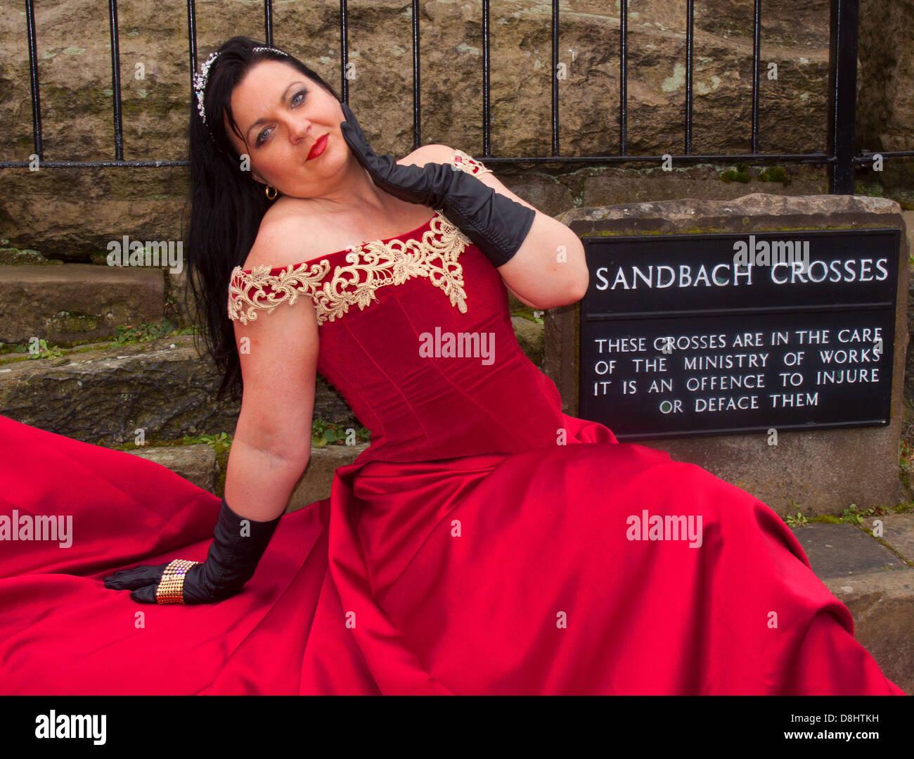 Dieses Stockfoto: Die Frau im roten Kleid vor sandbach Kreuze, Marktplatz, Sandbach, Cheshire, England, CW 11 1 AN - D8HTKH