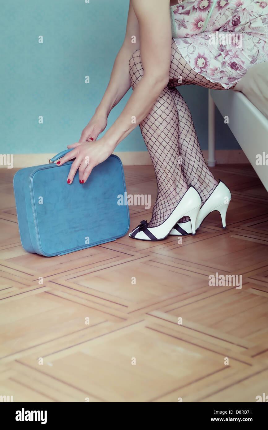 eine Frau in einem Negligé sitzt auf einem Bett mit einem Koffer Stockbild