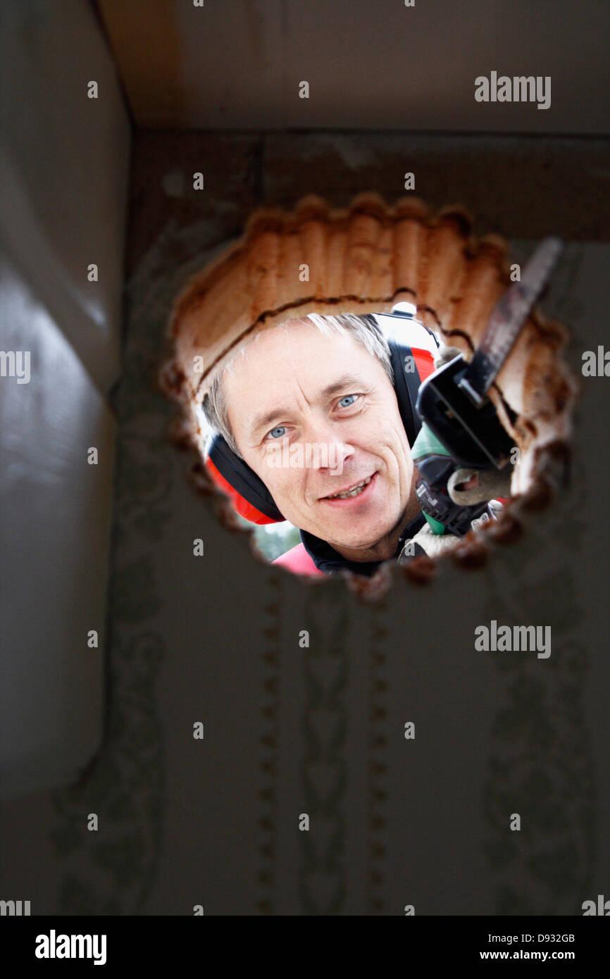 Lächelnder Mann Loch sägen Stockbild