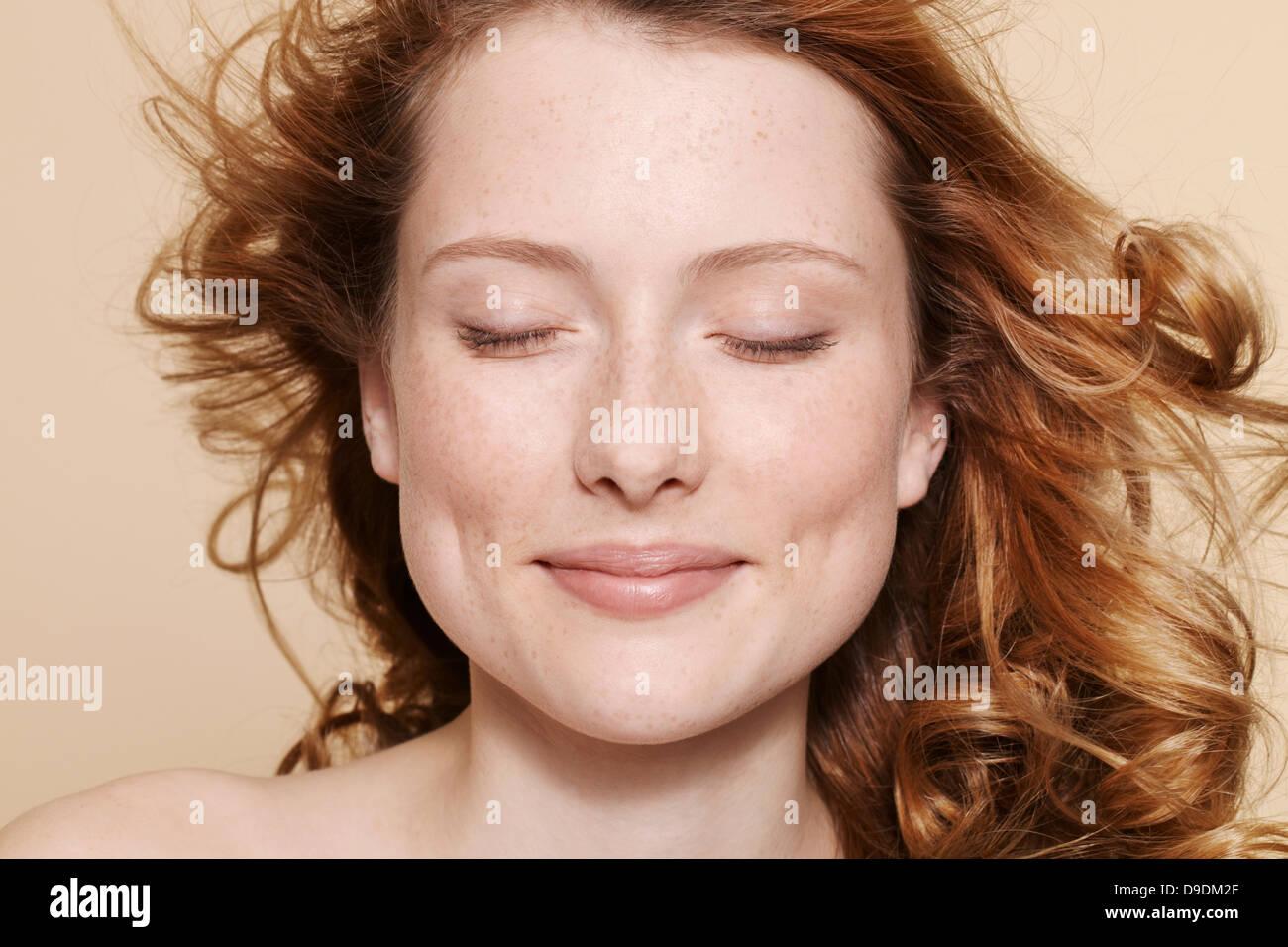 Studioaufnahme der jungen Frau mit lockigen roten Haaren, Augen geschlossen Stockbild