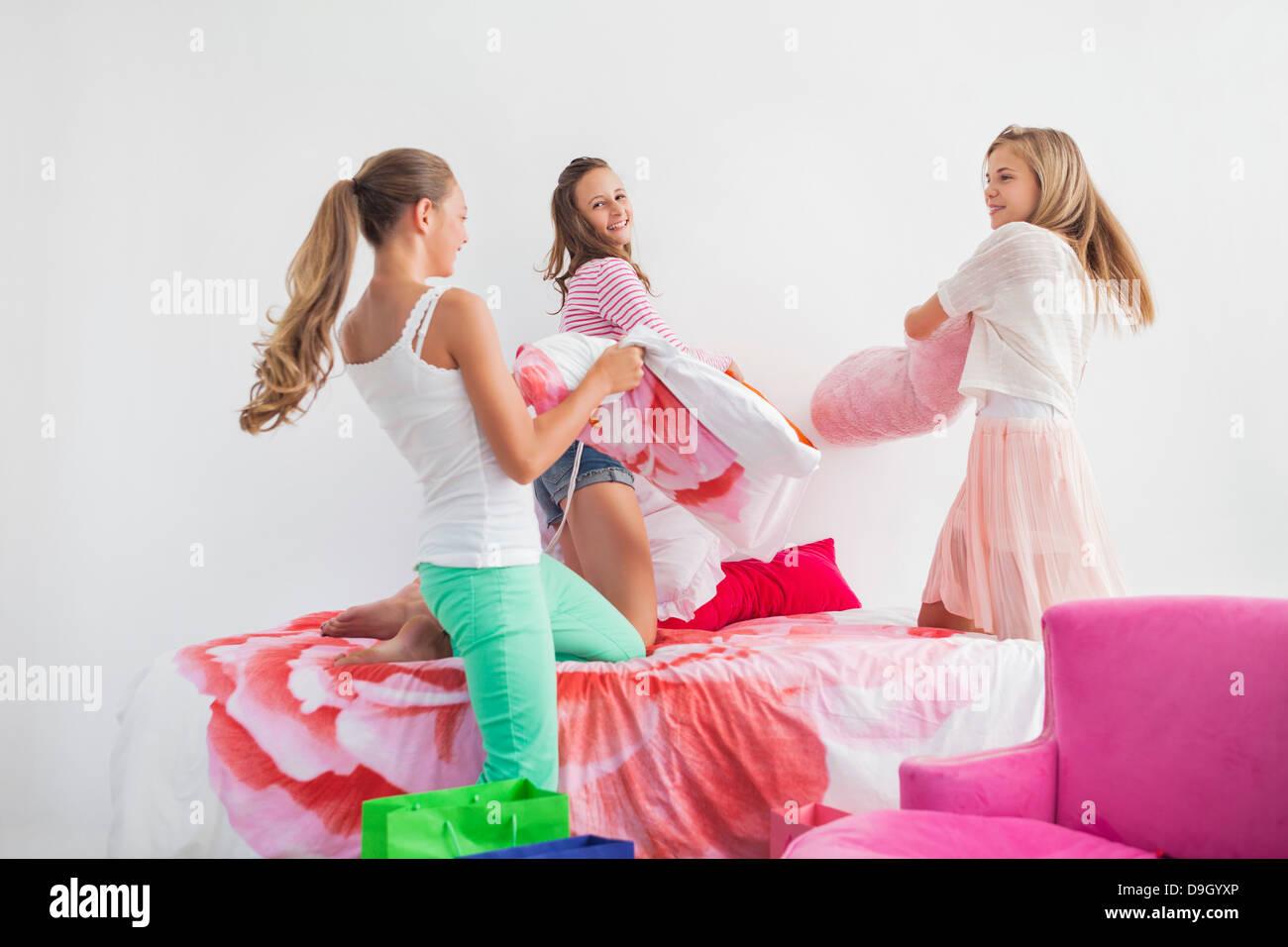 Mädchen, die Kissen auf dem Bett bei einer Pyjama-Party zu kämpfen Stockbild
