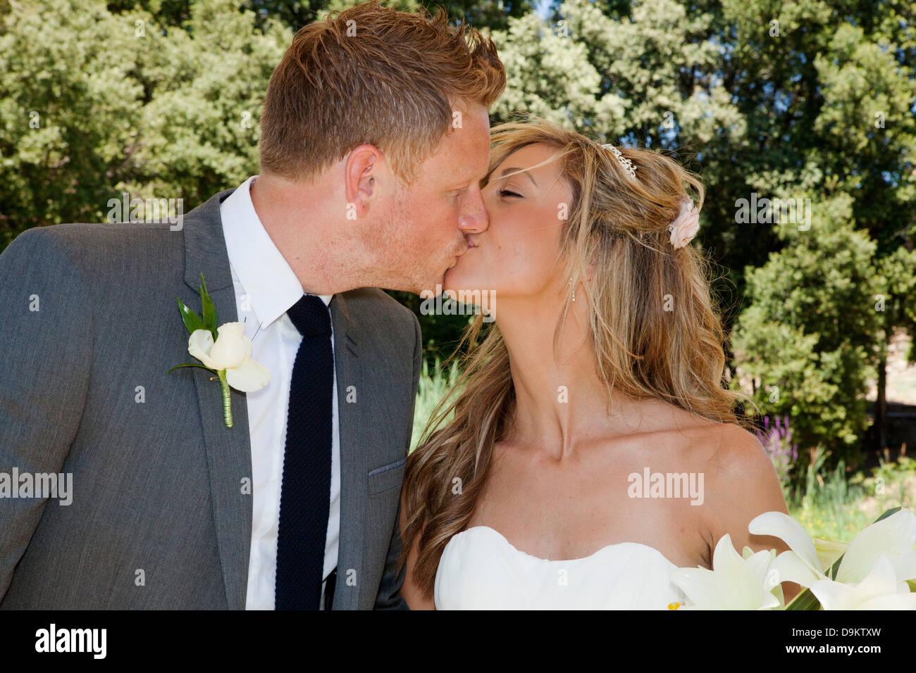 Mitte Erwachsenen Braut und Bräutigam küssen am Hochzeitstag Stockbild