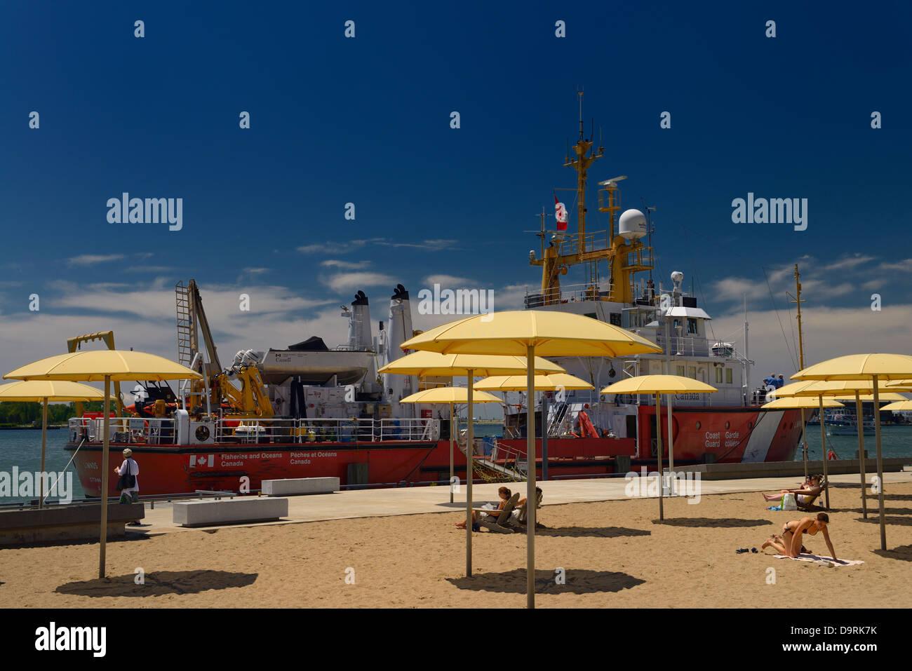 Sand und Sonnenschirme im H2O städtischen Park in Toronto Harbourfront mit Schiff der Küstenwache am Lake Stockbild