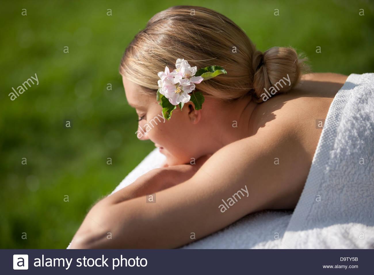 Eine junge Frau auf einem Massagetisch mit Apfelblüte im Haar, Augen geschlossen Stockbild
