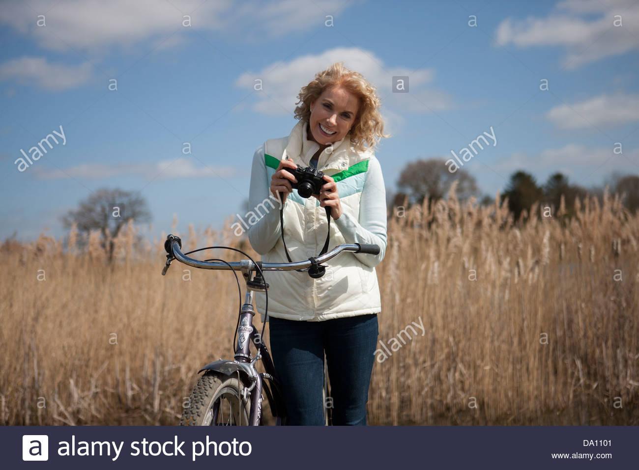 Eine reife Frau, Radfahren, eine Kamera zu halten Stockbild