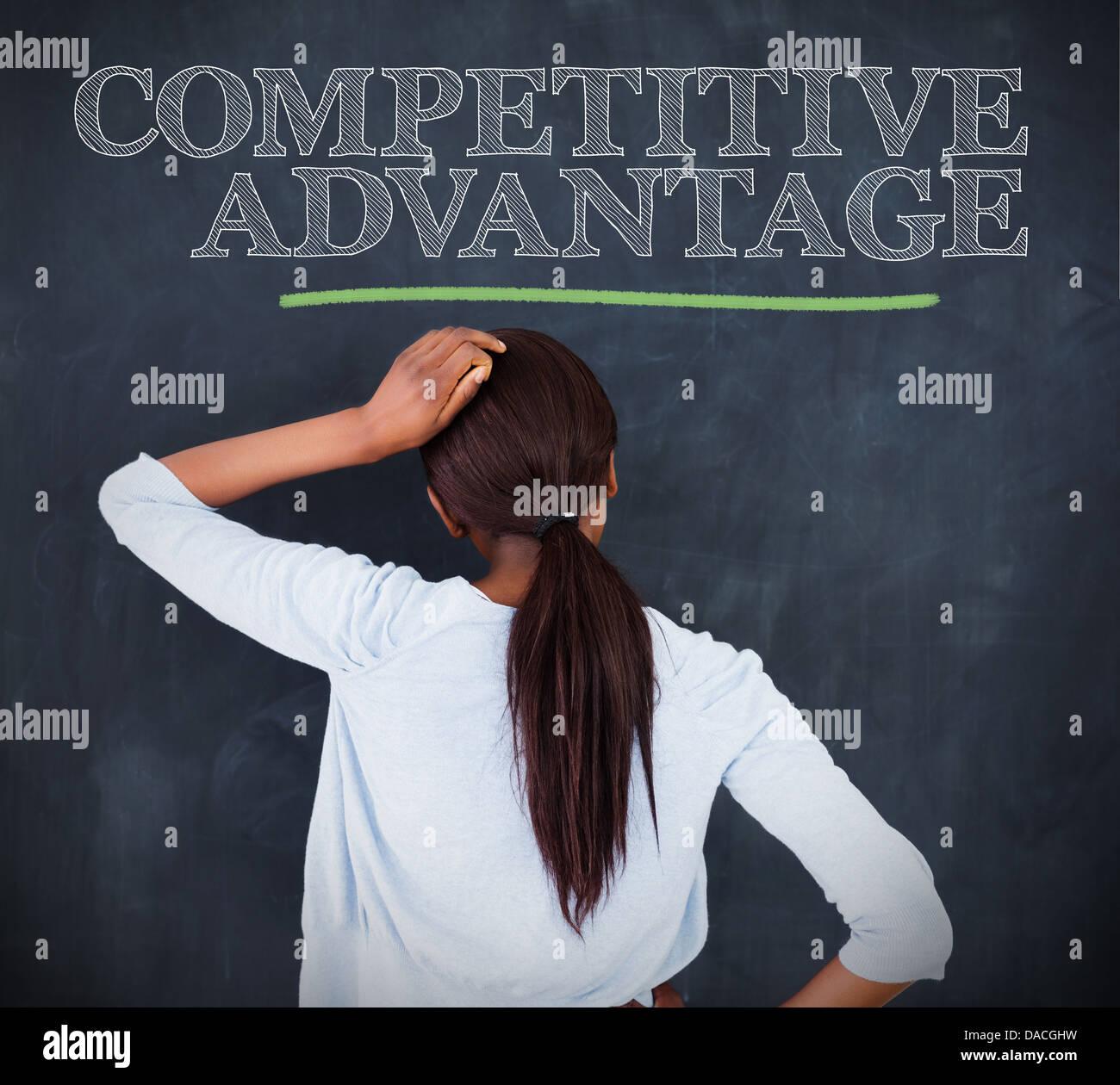 Frau das Wort Wettbewerbsvorteil betrachten Stockbild