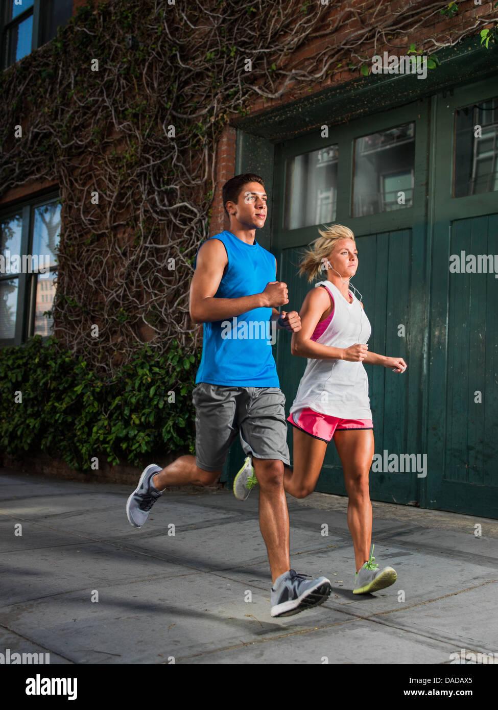 Junger Mann und junge Frau läuft auf städtischen Straße Stockbild