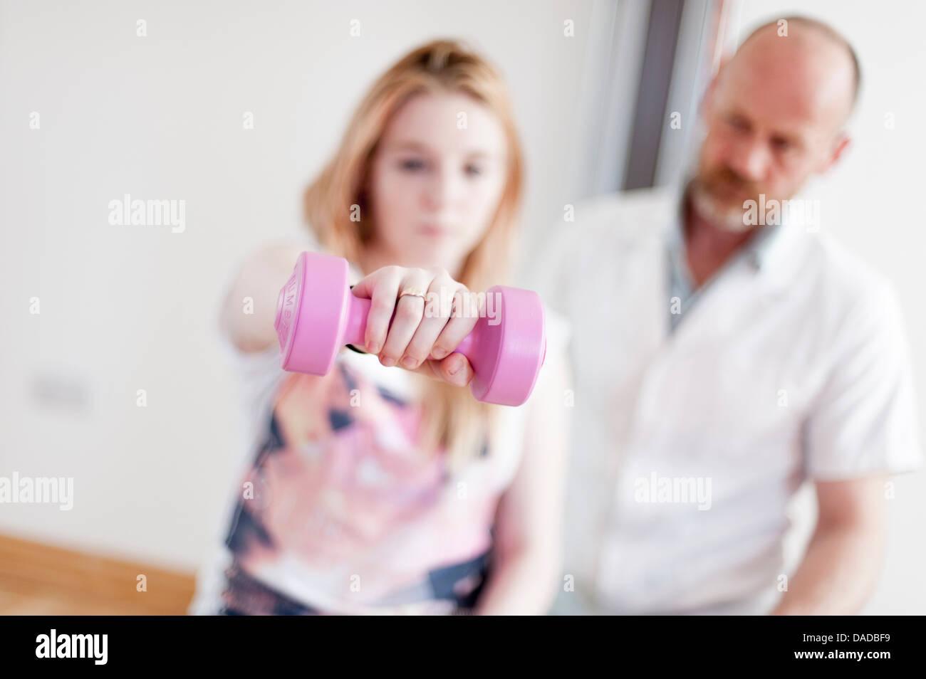 Junge Frau, die das Training mit Hanteln, geleitet von reifer Mann Stockbild