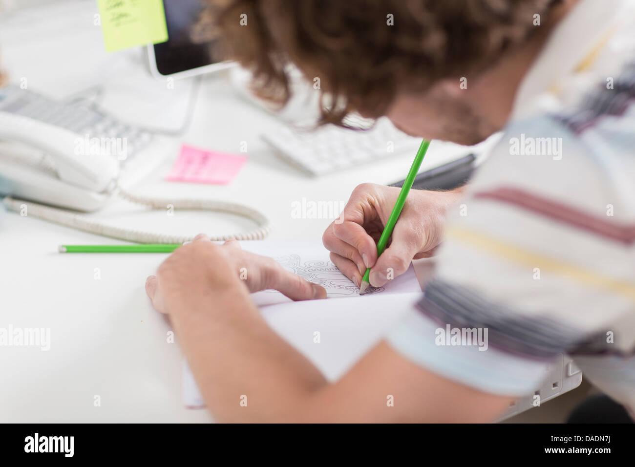 Junge kreative zeichnen Pläne am Schreibtisch, Nahaufnahme Stockbild