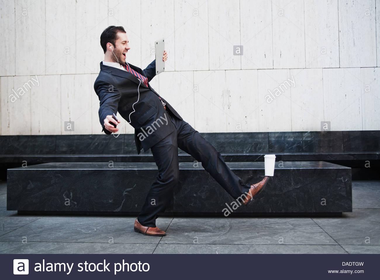 Geschäftsmann hält Laptop und balancing Kaffee auf seinem Fuß Stockbild