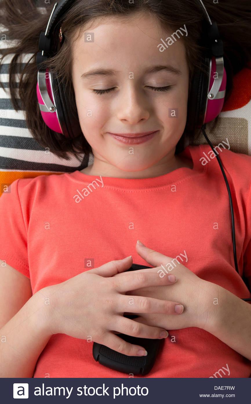 Mädchen mit Kopfhörern, Augen geschlossen Stockbild