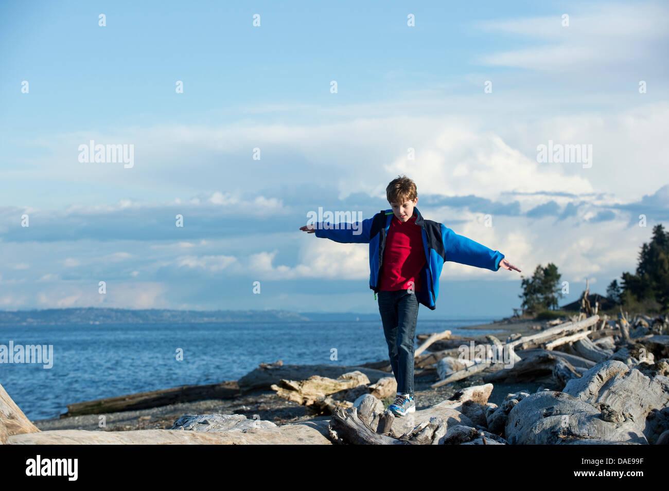 Kleiner Junge balancieren auf Baumstamm an Küste Stockbild