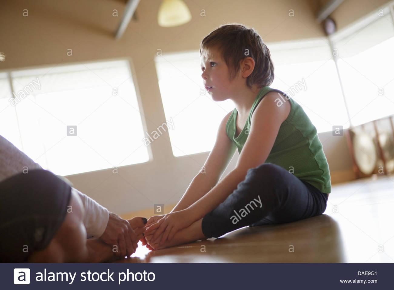 Junges Mädchen mit Mutter praktizieren Yoga im Innenbereich Stockbild