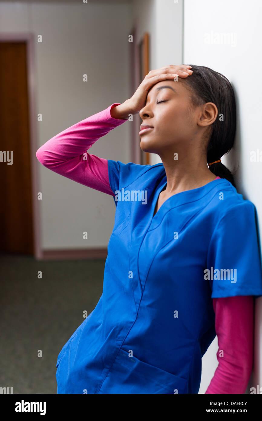 Krankenschwester mit geschlossenen Augen und hand auf Kopf im Krankenhausflur Stockbild