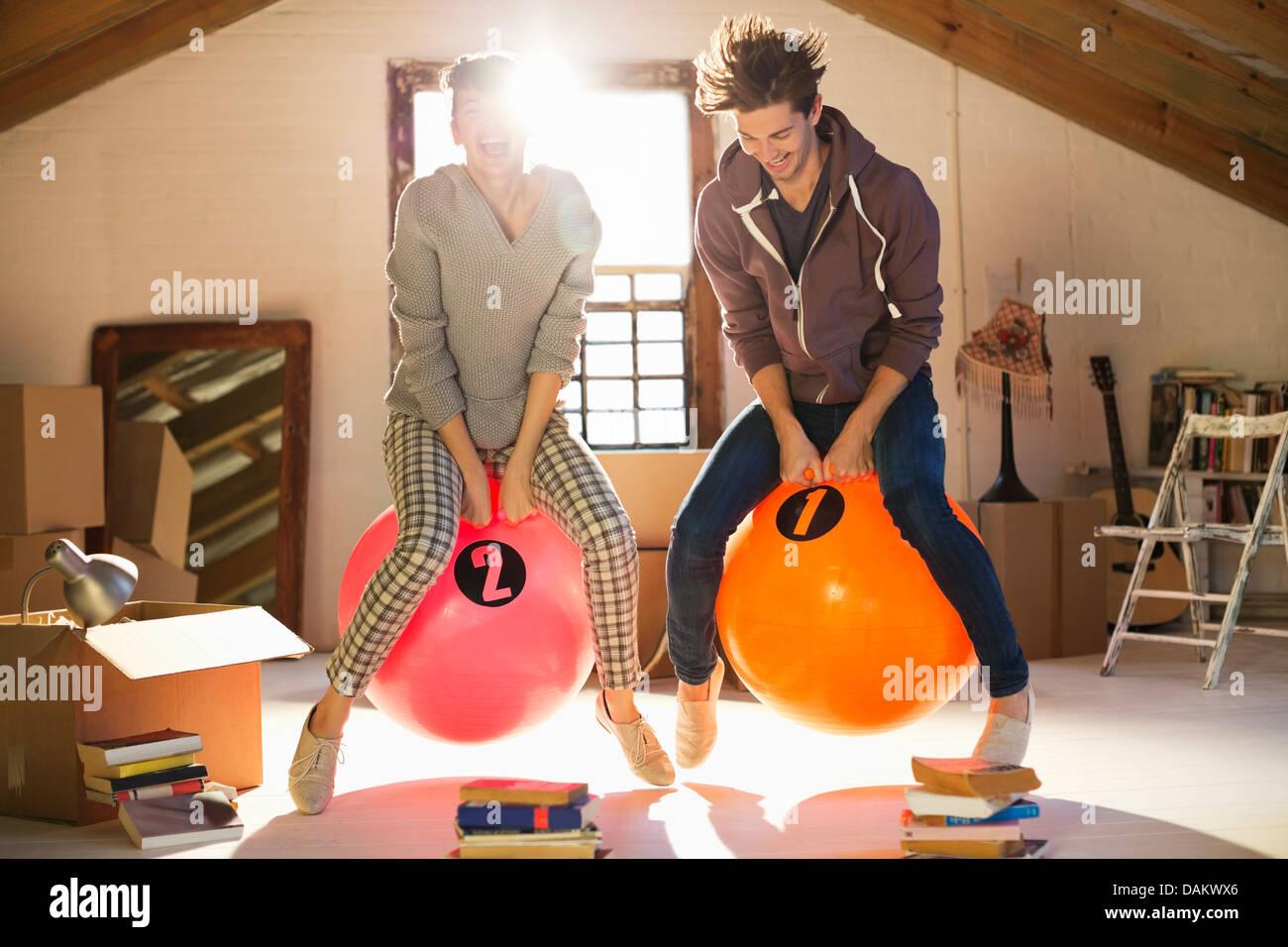 Paar springen auf Gymnastikbällen zusammen Stockfoto