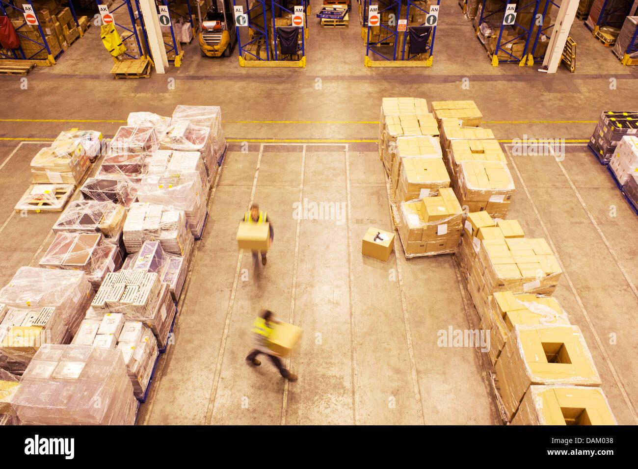Verschwommene Sicht der Arbeitnehmer tragen Kisten im Lager Stockbild