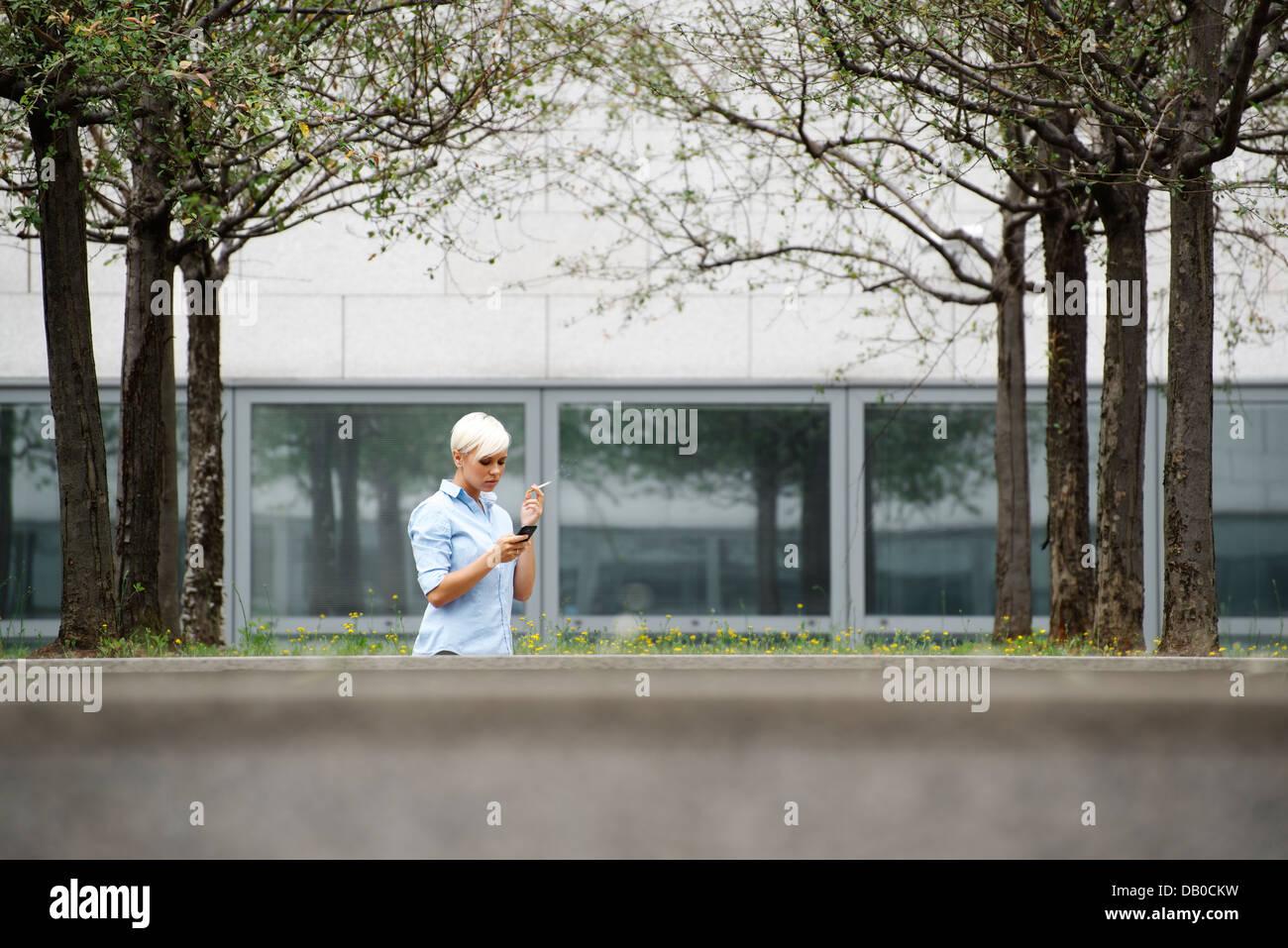 junge Geschäftsfrau qualmender Zigarette während des Bürogebäudes ausbrechen. Wide shot, Textfreiraum Stockbild